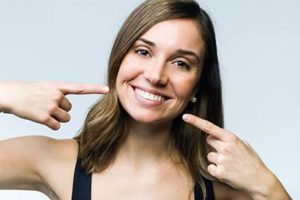 A woman points to her smile after getting cosmetic dentistry in Gulfgate, TX