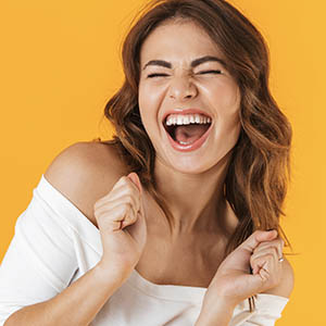 A woman laughs as she thinks about the dental implant services at Lovett Dental Gulfgate