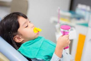 A little girl gets fluoride treatments in TX at a dentist's office