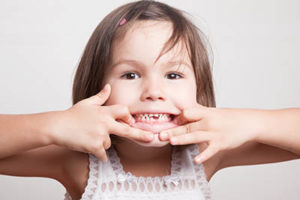 A little girl pulls at the sides of her mouth to show the results of pediatric dentistry in Gulfgate, TX