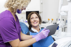 at a routine check up a woman talks to her dentist about dental checkups in gulfgate tx