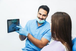 man explaining what a root canal treatment is to a patient